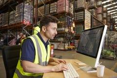 Άτομο που εργάζεται στο επιτόπιο γραφείο σε μια αποθήκη εμπορευμάτων διανομής