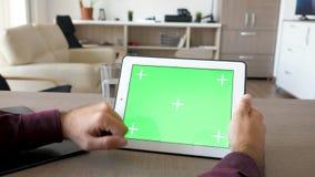 Άτομο που εργάζεται στο ψηφιακό PC ταμπλετών με την πράσινη χλεύη οθόνης επάνω απόθεμα βίντεο