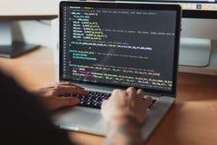 Άτομο που εργάζεται στο lap-top, προγραμματισμένος κώδικας για τον Ιστό στοκ φωτογραφία