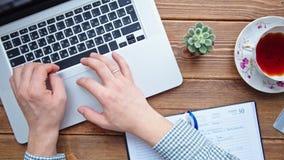 Άτομο που εργάζεται στο lap-top που τοποθετείται στο ξύλινο γραφείο απόθεμα βίντεο