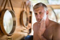 Άτομο που εφαρμόζει την κρέμα ξυρίσματος στο πρόσωπό του στο εξοχικό σπίτι κατά τη διάρκεια των διακοπών σαφάρι στοκ φωτογραφία