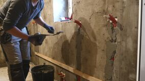 Άτομο που εφαρμόζει το ασβεστοκονίαμα σε έναν ξηρό τοίχο Επικονίαση εργατών οικοδομών εφαρμογή του /Plaster απόθεμα βίντεο