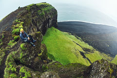 Άτομο που θέτει στον απότομο βράχο Dyrholaey, Ισλανδία Στοκ Φωτογραφίες