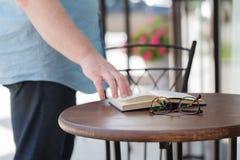 Άτομο που διαβάζει ένα βιβλίο με την κατανάλωση του καφέ ή του τσαγιού Στοκ φωτογραφία με δικαίωμα ελεύθερης χρήσης