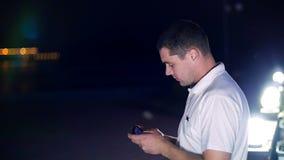Άτομο που διαβάζει ένα μήνυμα στο κινητό τηλέφωνό σας - κοντά στα φανάρια τη νύχτα απόθεμα βίντεο