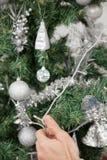 Άτομο που διακοσμεί το χριστουγεννιάτικο δέντρο με τα φω'τα νεράιδων Στοκ φωτογραφίες με δικαίωμα ελεύθερης χρήσης
