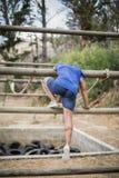 Άτομο που διασχίζει το σχοινί κατά τη διάρκεια της σειράς μαθημάτων εμποδίων Στοκ Φωτογραφία