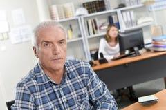 Άτομο που κάθεται ανώτερο στο γραφείο Στοκ Φωτογραφίες