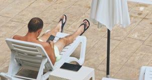 Άτομο που κάνει ηλιοθεραπεία στην καρέκλα από τη λίμνη φιλμ μικρού μήκους