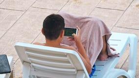 Άτομο που κάνει ηλιοθεραπεία στην καρέκλα από τη λίμνη απόθεμα βίντεο