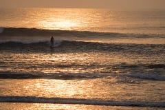 Άτομο που κάνει σερφ στο ωκεάνιο νερό στο χρόνο ηλιοβασιλέματος στοκ εικόνες με δικαίωμα ελεύθερης χρήσης