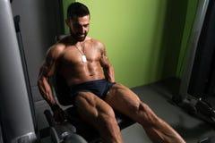 Άτομο που κάνει την καθισμένη άσκηση μπουκλών ποδιών στη γυμναστική Στοκ Εικόνες