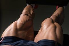 Άτομο που κάνει την καθισμένη άσκηση μπουκλών ποδιών στη γυμναστική Στοκ Φωτογραφίες