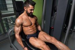 Άτομο που κάνει την καθισμένη άσκηση μπουκλών ποδιών στη γυμναστική Στοκ φωτογραφία με δικαίωμα ελεύθερης χρήσης