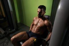 Άτομο που κάνει την καθισμένη άσκηση μπουκλών ποδιών στη γυμναστική Στοκ εικόνες με δικαίωμα ελεύθερης χρήσης