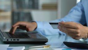 Άτομο που κάνει τη σε απευθείας σύνδεση πληρωμή στον υπολογιστή, που χρησιμοποιεί την κάρτα για τις τραπεζικές υπηρεσίες Διαδικτύ φιλμ μικρού μήκους