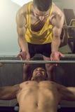 Άτομο που κάνει το βάρος που ανυψώνει με τον προσωπικό εκπαιδευτή Στοκ φωτογραφία με δικαίωμα ελεύθερης χρήσης