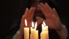 Άτομο που κάνει το μαγικό τελετουργικό κινηματογράφηση σε πρώτο πλάνο αρκετοί κερί και παλαιό βιβλίο ο νεκρομάντης πετά τις περιό φιλμ μικρού μήκους