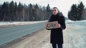 Άτομο που κάνει ωτοστόπ στη χειμερινή εθνική οδό με το πιάτο χαρτονιού απόθεμα βίντεο