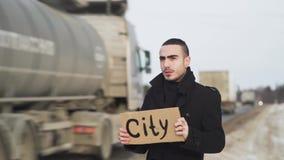 Άτομο που κάνει ωτοστόπ στη χειμερινή εθνική οδό με το πιάτο χαρτονιού και που ζητά κάποιο για να σταματήσει την κινηματογράφηση  φιλμ μικρού μήκους