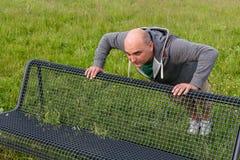 Άτομο που κάνει pushups υπαίθρια σε έναν πάγκο Στοκ Εικόνες