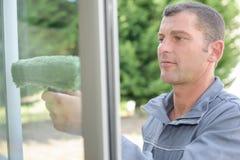 Άτομο που καθαρίζει ένα παράθυρο στοκ φωτογραφίες με δικαίωμα ελεύθερης χρήσης