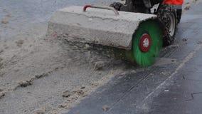 Άτομο που καθαρίζει το βρώμικο χιόνι στο δρόμο με το διαβασμένο άροτρο χιονιού με τη βούρτσα απόθεμα βίντεο