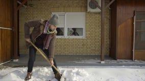 Άτομο που καθαρίζει φτυαρίζοντας το φρέσκο χιόνι στο ναυπηγείο