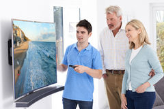 Άτομο που καταδεικνύει τη νέα τηλεόραση για να ωριμάσει το ζεύγος στο σπίτι Στοκ Εικόνες