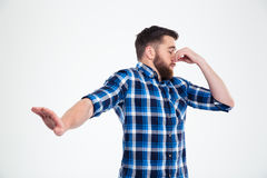 Άτομο που καλύπτει τη μύτη του και που παρουσιάζει χειρονομία στάσεων με το φοίνικα Στοκ Εικόνες