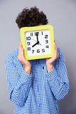 Άτομο που καλύπτει το πρόσωπό του με το μεγάλο ρολόι Στοκ Εικόνες
