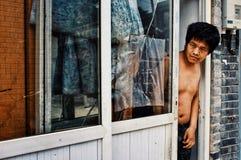 Άτομο που κοιτάζει έξω από το σπίτι του στην οδό σε μια χαρακτηριστική πόλη hutong στοκ εικόνες