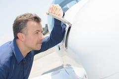 Άτομο που κοιτάζει αδιάκριτα στο διαμέρισμα airoplane Στοκ Φωτογραφίες