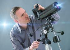 Άτομο που κοιτάζει μέσω του τηλεσκοπίου στοκ εικόνα