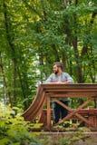 Άτομο που κοιτάζει μακριά στεμένος στην ξύλινη γέφυρα στο δάσος Στοκ Φωτογραφίες