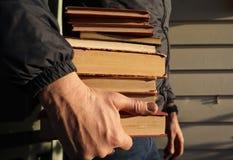 Άτομο που κρατά έναν σωρό των βιβλίων ανάγνωσης διαθέσιμων στοκ φωτογραφία