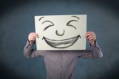 Άτομο που κρατά ένα έγγραφο με το πρόσωπο smiley Στοκ Φωτογραφίες