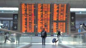 Άτομο που κρατά ένα διαβατήριο στο χέρι του που πηγαίνει κοντά στη μεγάλη οθόνη προγράμματος χρονοδιαγράμματος στον αερολιμένα απόθεμα βίντεο