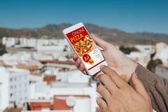 Άτομο που κρατά ένα κινητό τηλέφωνο στο χέρι με τις αγορές app πιτσών στην οθόνη Στοκ εικόνες με δικαίωμα ελεύθερης χρήσης