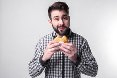 Άτομο που κρατά ένα κομμάτι του χάμπουργκερ ο σπουδαστής τρώει το γρήγορο φαγητό μη χρήσιμα τρόφιμα πολύ πεινασμένος τύπος Στοκ Φωτογραφία