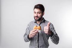 Άτομο που κρατά ένα κομμάτι του χάμπουργκερ ο σπουδαστής τρώει το γρήγορο φαγητό μη χρήσιμα τρόφιμα πολύ πεινασμένος τύπος Στοκ εικόνες με δικαίωμα ελεύθερης χρήσης