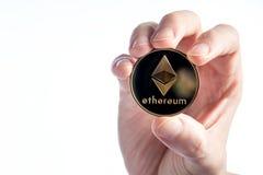 Άτομο που κρατά ένα νόμισμα Ethereum αιθέρα σε ένα άσπρο υπόβαθρο στοκ εικόνες με δικαίωμα ελεύθερης χρήσης