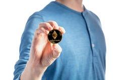 Άτομο που κρατά ένα νόμισμα Ethereum αιθέρα σε ένα άσπρο υπόβαθρο στοκ εικόνα