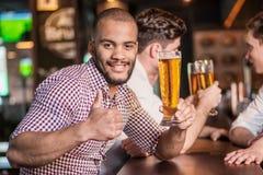 Άτομο που κρατά ένα ποτήρι της μπύρας διαθέσιμο καθμένος στο φραγμό και Στοκ Εικόνα