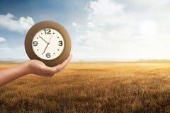 Άτομο που κρατά ένα ρολόι με το ξηρό υπόβαθρο τομέων χλόης Στοκ Εικόνα