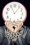 Άτομο που κρατά ένα ρολόι αντί του προσώπου του με τα χέρια του που αλυσοδένονται Στοκ εικόνα με δικαίωμα ελεύθερης χρήσης
