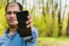 Άτομο που κρατά ένα τηλέφωνο στο χέρι του Στοκ Εικόνες