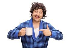 Άτομο που κρατά ένα φλυτζάνι και που δείχνει το Στοκ Εικόνα