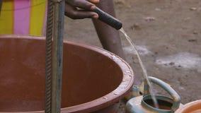 Άτομο που κρατά ένα χαμηλής πιέσεως νερό βρύσης, τρώγλη του Κόνακρι φιλμ μικρού μήκους