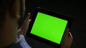 Άτομο που κρατά ένα PC ταμπλετών με την πράσινη οθόνη στο μαύρο υπόβαθρο απόθεμα βίντεο